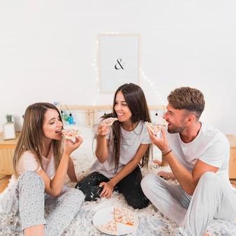 Lächelnde junge paare, die pizza auf bett mit verbreiteten weißen federn essen