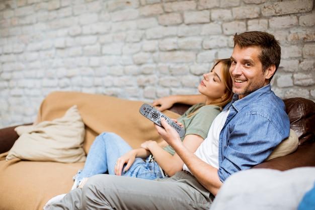 Lächelnde junge paare, die sich zu hause entspannen und fernsehen