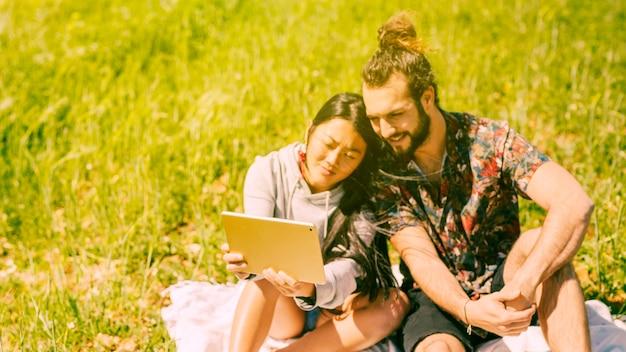 Lächelnde junge paare, die tablette auf dem gebiet halten