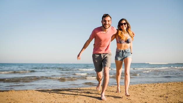 Lächelnde junge paare, die zusammen auf strand laufen