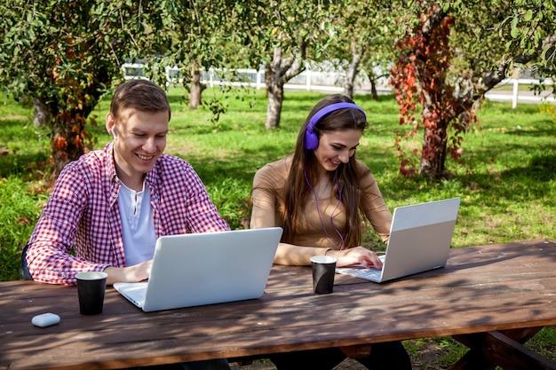Lächelnde junge paare verbringen zeit zusammen im park, lernen und arbeiten, während sie mit einem laptop an einem holztisch sitzen. kerl mit einem mädchen mit gadgets im park