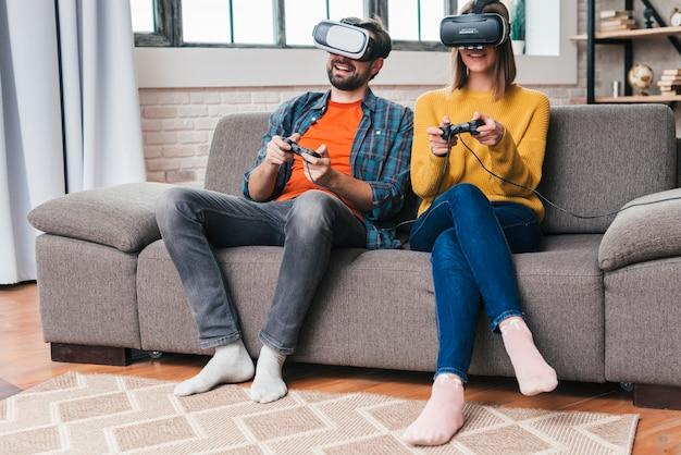 Lächelnde junge paare, welche die gläser der virtuellen realität spielen das videospiel tragen