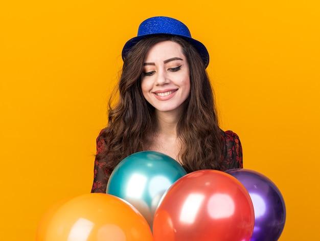 Lächelnde junge partyfrau mit partyhut, die hinter luftballons steht und auf sie herabschaut, isoliert auf orangefarbener wand