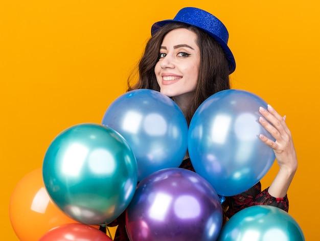 Lächelnde junge partyfrau mit partyhut, die hinter luftballons steht und einen berührt, der nach vorne isoliert auf oranger wand schaut