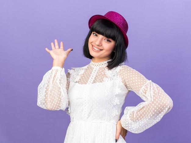 Lächelnde junge partyfrau mit partyhut, die nach vorne schaut und die hand auf der taille hält, die leere hand isoliert auf lila wand zeigt