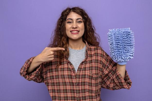 Lächelnde junge putzfrau hält und zeigt auf putzlappen