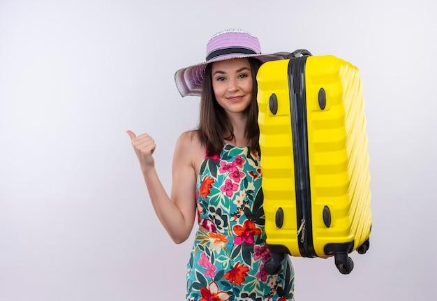 Lächelnde junge reisende frau, die daumen oben zeigt koffer auf isolierter weißer wand hält