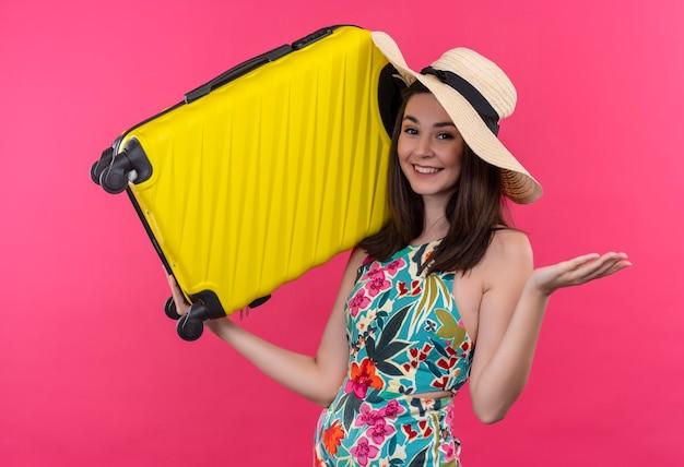 Lächelnde junge reisende frau, die hut hält koffer auf isolierter rosa wand hält