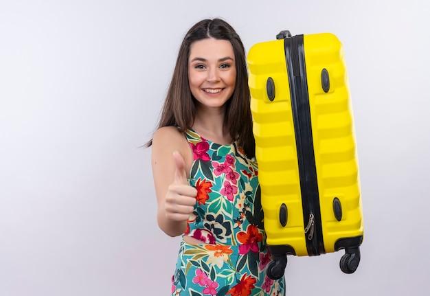 Lächelnde junge reisende frau, die koffer hält daumen oben auf isolierter weißer wand zeigt