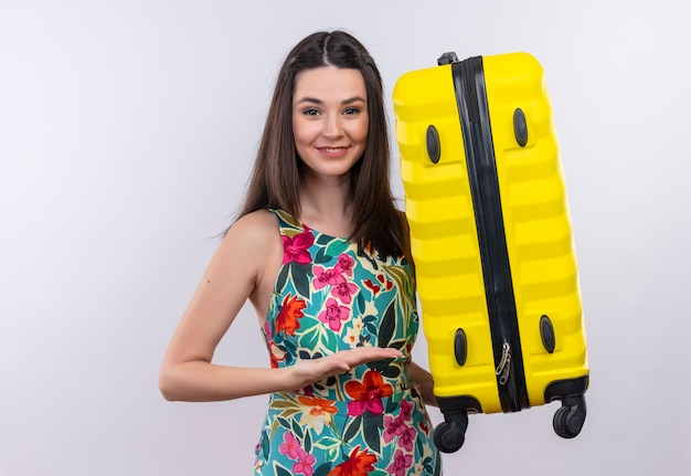 Lächelnde junge reisende frau, die koffer hält, der mit hand am koffer auf isolierter weißer wand zeigt