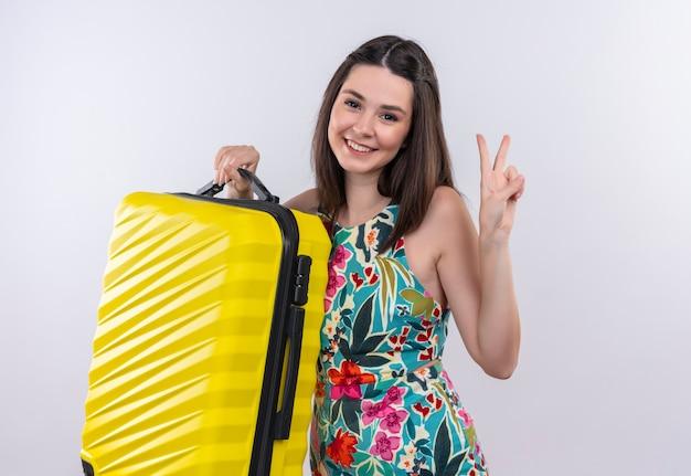 Lächelnde junge reisende frau, die mehrfarbiges kleid hält, das eine mobile tasche hält und friedensgeste auf weißer wand zeigt