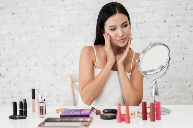 Lächelnde junge schöne frau, die auf spiegel mit make-up-kosmetik zu hause gesetzt schaut