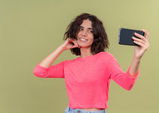 Lächelnde junge schöne frau, die hand auf kinn setzt und selfie mit handy auf isolierter grüner wand nimmt