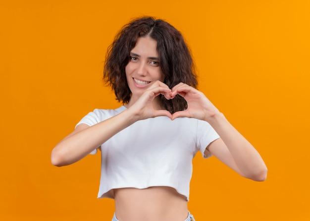 Lächelnde junge schöne frau, die herzzeichen auf lokalisierter orange wand tut