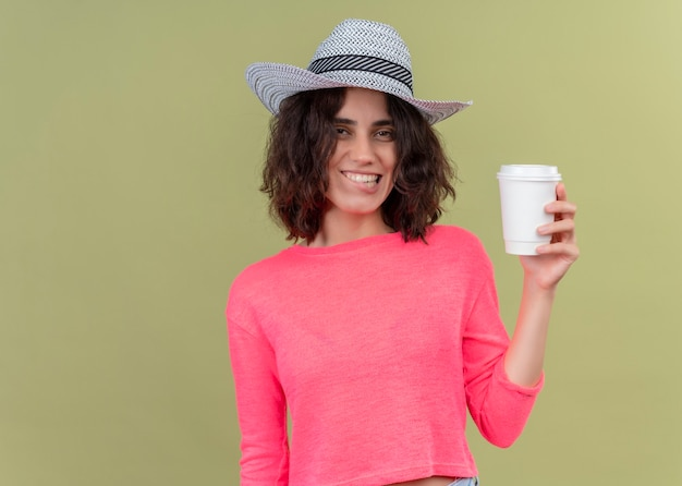 Lächelnde junge schöne frau, die hut hält, der plastikkaffeetasse auf isolierter grüner wand mit kopienraum hält