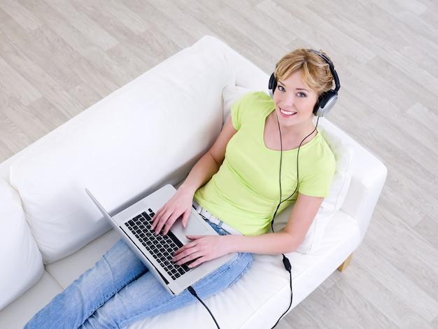 Lächelnde junge schöne frau, die musik im kopfhörer vom laptop - hoher winkel hört