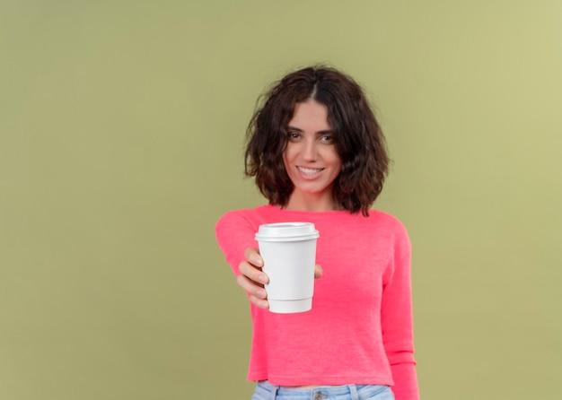 Lächelnde junge schöne frau, die plastikkaffeetasse hält und sie auf isolierter grüner wand mit kopienraum ausdehnt