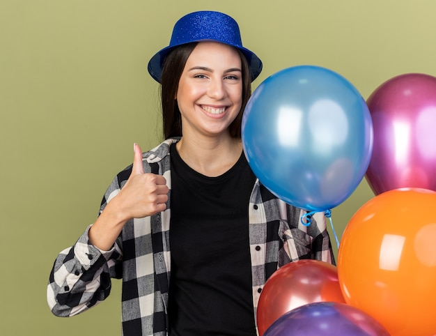 Lächelnde junge schöne frau mit blauem hut, die in der nähe von ballons steht und daumen nach oben zeigt, isoliert auf olivgrüner wand