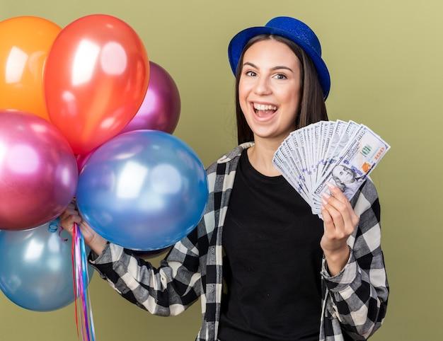 Lächelnde junge schöne frau mit blauem hut hält luftballons mit bargeld isoliert auf olivgrüner wand
