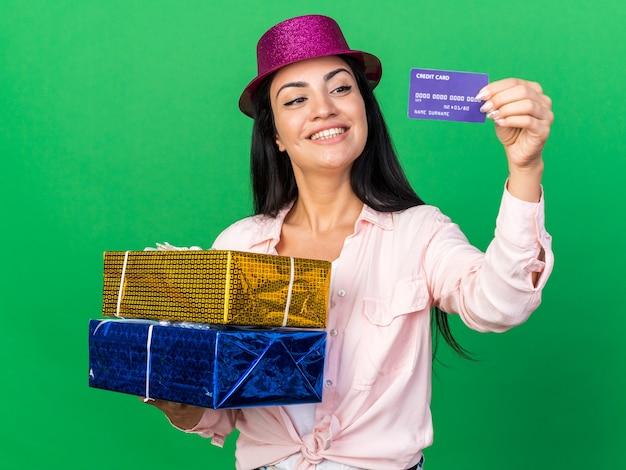 Lächelnde junge schöne frau mit partyhut mit geschenkboxen mit kreditkarte isoliert auf grüner wand