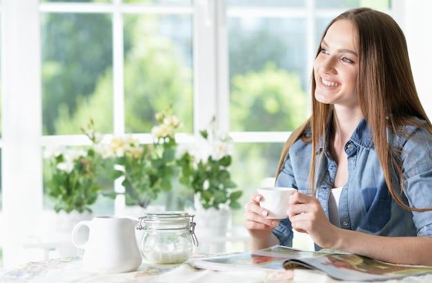 Lächelnde junge schöne frau mit zeitschrift in der küche