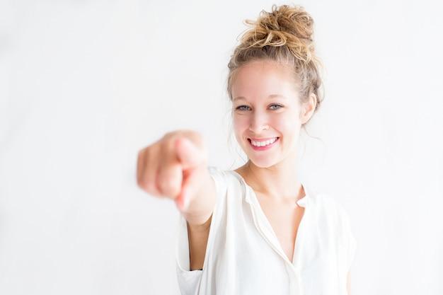 Lächelnde junge schöne frau zeigt auf sie