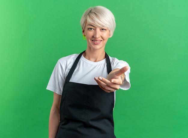 Lächelnde junge schöne friseurin in uniform, die die hand vor die kamera hält, isoliert auf grünem hintergrund
