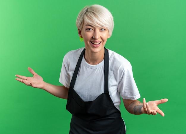 Lächelnde junge schöne friseurin in uniform, die hände auf grünem hintergrund ausbreitet