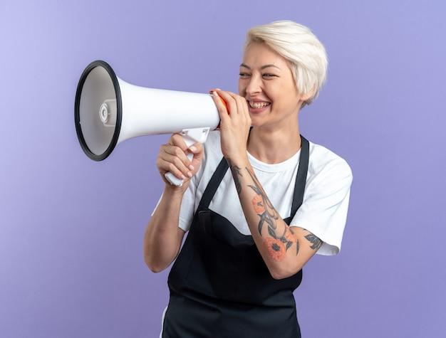 Lächelnde junge schöne friseurin in uniform spricht über lautsprecher isoliert auf blauem hintergrund