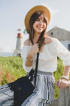 Lächelnde junge schöne stilvolle frau, frühling sommer modetrend, boho-stil, strohhut, landschaftswochenende, sonnige, schwarze geldbörse