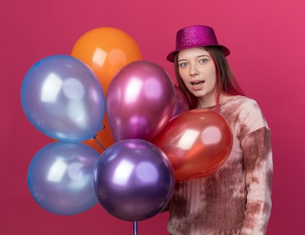 Lächelnde junge schöne tragende partyhut mit luftballons isoliert auf rosa wand