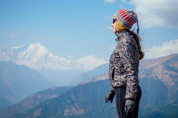 Lächelnde junge schöne und aktive frau beim trekking in den bergen. das konzept der aktiven erholung und des tourismus in den bergen. trekking in nepal himalaya