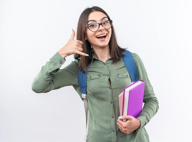 Lächelnde junge schulfrau mit brille mit rucksack, die bücher hält, die telefonanrufgeste zeigen