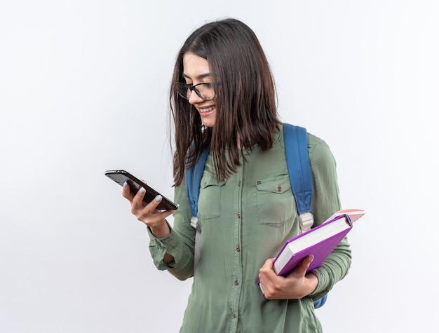Lächelnde junge schulfrau mit brille mit rucksack, die bücher hält und auf das telefon in der hand schaut