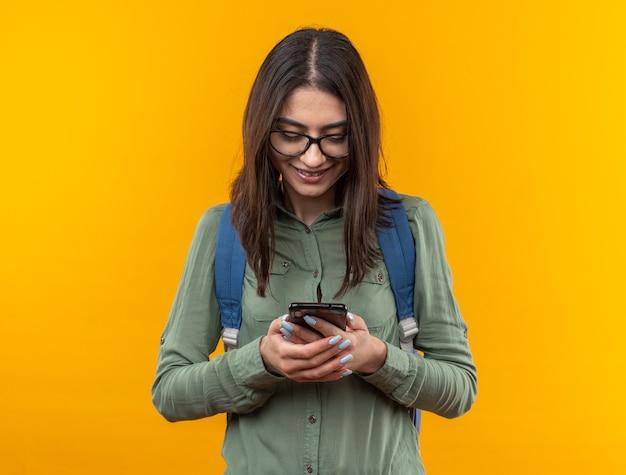 Lächelnde junge schulfrau mit rucksack mit brille, die das telefon hält und anschaut