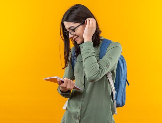 Lächelnde junge schulfrau mit rucksack mit brille, die notebook hält und betrachtet