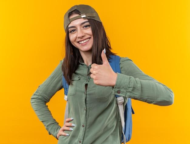 Lächelnde junge schulfrau mit rucksack mit mütze, die den daumen zeigt und die hand auf die hüfte legt