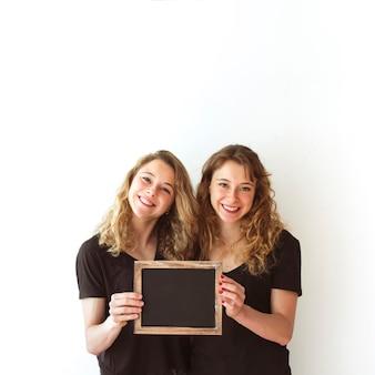 Lächelnde junge schwester, die zusammen den unbelegten schiefer getrennt über weißem hintergrund anhält