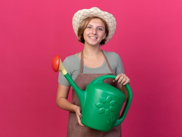Lächelnde junge slawische gärtnerin mit gartenhut hält gießkanne