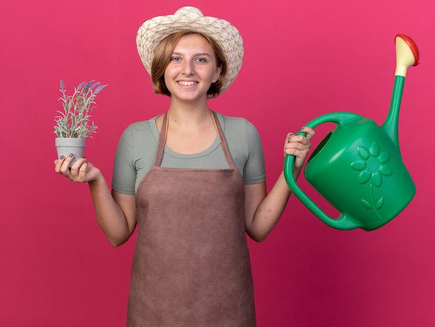 Lächelnde junge slawische gärtnerin mit gartenhut mit gießkanne und blumen im blumentopf