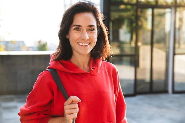 Lächelnde junge sportlerin, die einen hoodie trägt, der draußen geht und sporttasche trägt