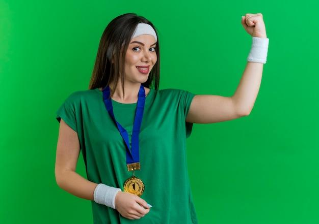 Lächelnde junge sportliche frau, die stirnband und armbänder mit medaille um den hals trägt und starke geste sucht