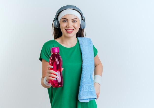 Lächelnde junge sportliche frau, die stirnband und armbänder und kopfhörer hält, die wasserflasche mit handtuch auf schulter lokalisiert auf weißer wand mit kopienraum halten