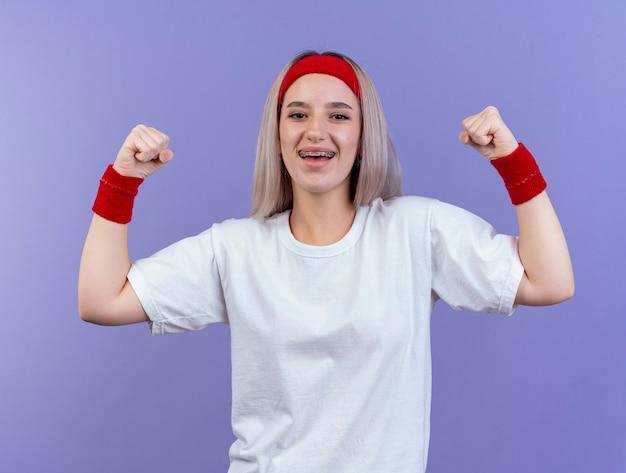 Lächelnde junge sportliche frau mit zahnspangen, die stirnband und armbänder spannen, spannt bizeps lokalisiert auf lila wand