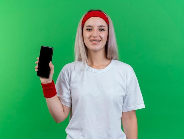 Lächelnde junge sportliche frau mit zahnspangen, die stirnband und armbänder tragen, hält telefon lokalisiert auf grüner wand