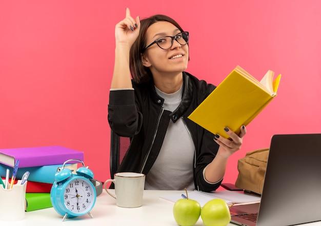 Lächelnde junge studentin, die eine brille trägt, die am schreibtisch mit universitätswerkzeugen hält buch hält hausaufgaben mit erhöhtem finger lokalisiert auf rosa wand