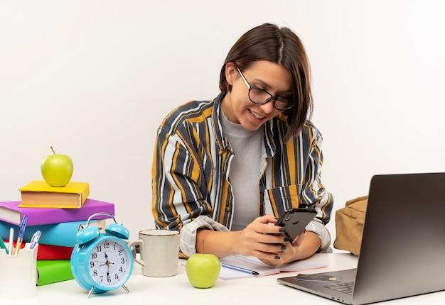Lächelnde junge studentin, die eine brille trägt, die am schreibtisch mit universitätswerkzeugen unter verwendung des auf weißer wand isolierten mobiltelefons sitzt