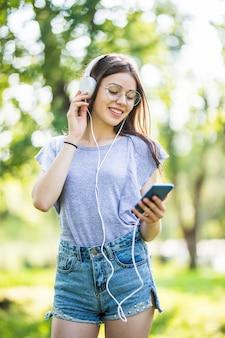 Lächelnde junge studentin mit rucksack, der handy hält, im park spaziert und musik mit kopfhörern hört