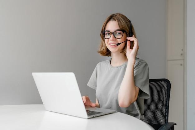 Lächelnde junge studentin tragen drahtloses headset mit laptop für online-bildung