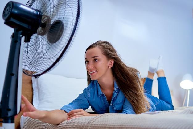 Lächelnde junge süße frau, die im bett im schlafzimmer im sonnigen heißen sommertag liegt und frische luft in der front des arbeitenden elektrischen ventilators genießt